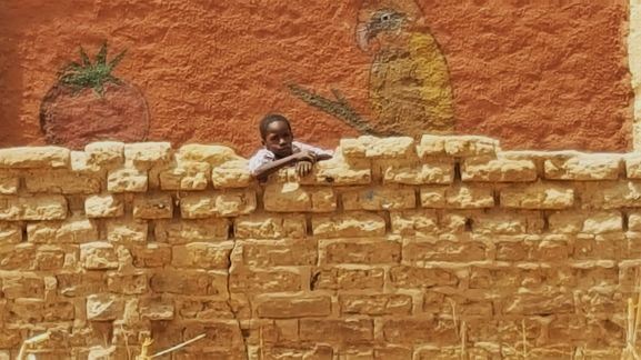 A young man propping up the mud wall next to the school.