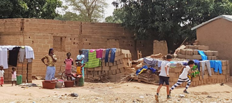The women are doing the laundry using the concrete bricks to dry it.